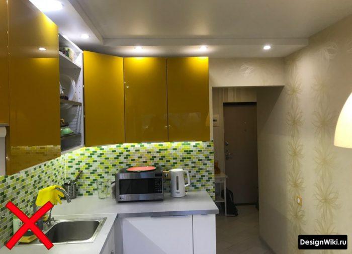 Глянцевая оранжевая кухня с бежевыми обоями с узором из цветов