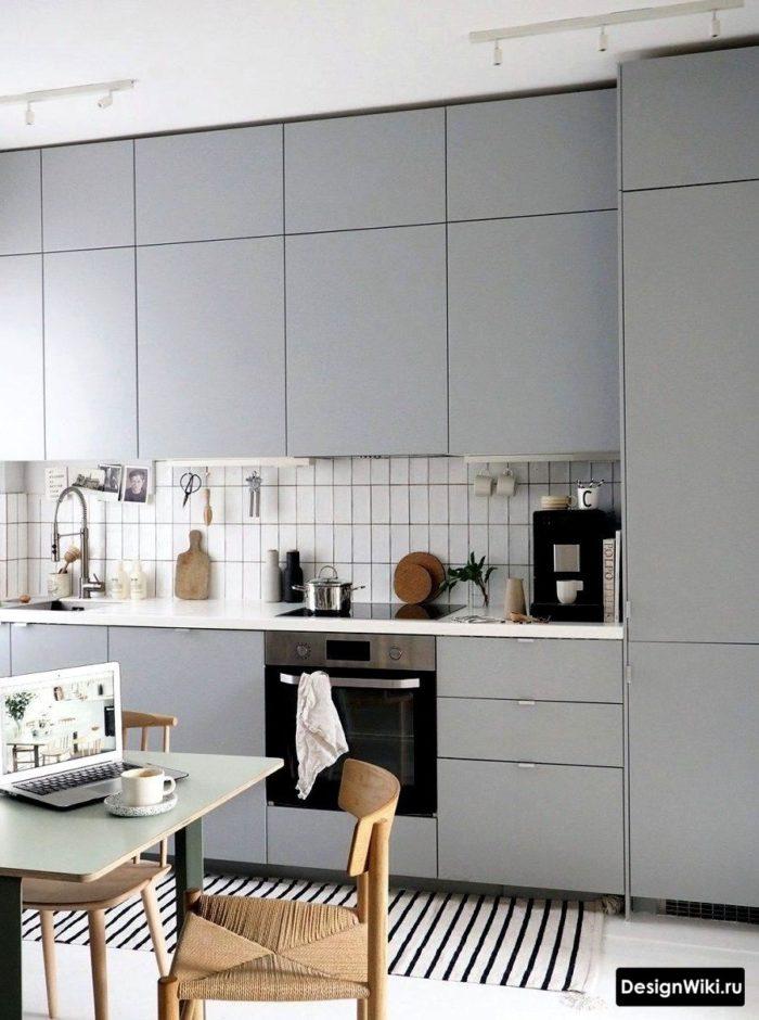 кухня в скандинавском стиле со светло-серыми матовыми фасадами под потолок