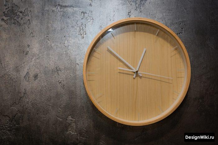 Деревянные часы на черной декоративной штукатурке