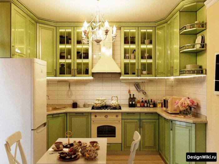 Оливковая кухня с прозрачными верхними шкафами