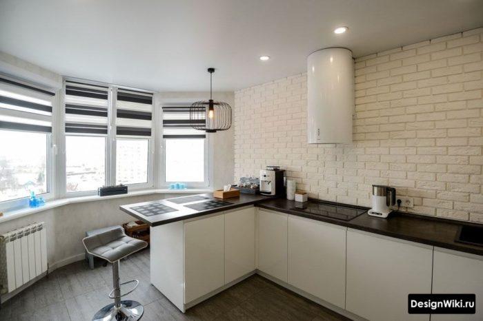 Белая кухня без верхних шкафов с черно-белыми рулонными шторами