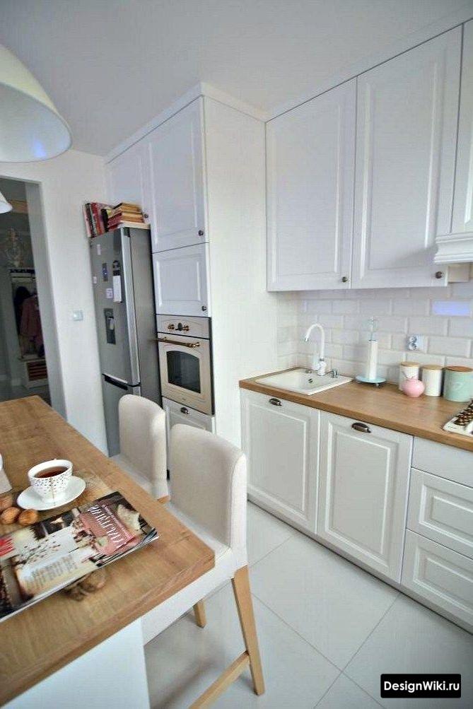 Белая кухня в стиле неоклассика с деревянной столешницей