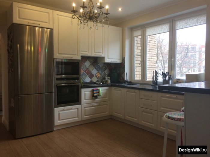 Угловая кухня в стиле неоклассика с мойкой у окна