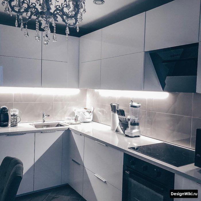 Интерьер белой кухни с мойкой в углу
