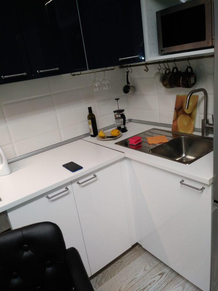 Маленькая белая кухня с мойкой в углу
