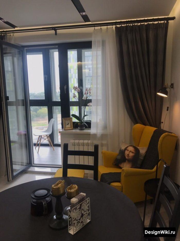 Плотные длинные шторы и тюль на окне с балконом