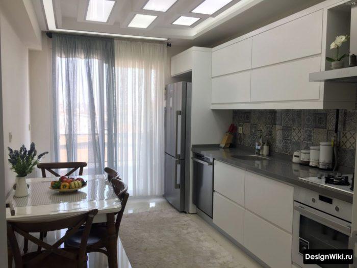 Современная белая кухня с балконом и тюлем