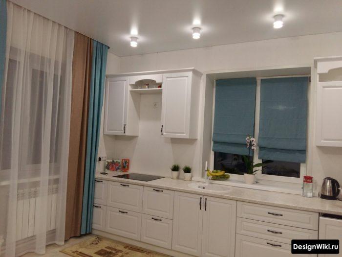 Сочетание голубых и коричневых штор на кухне с балконом