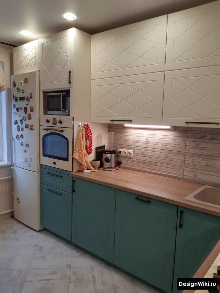 Угловая бежево-голубая кухня с холодильником возле стены
