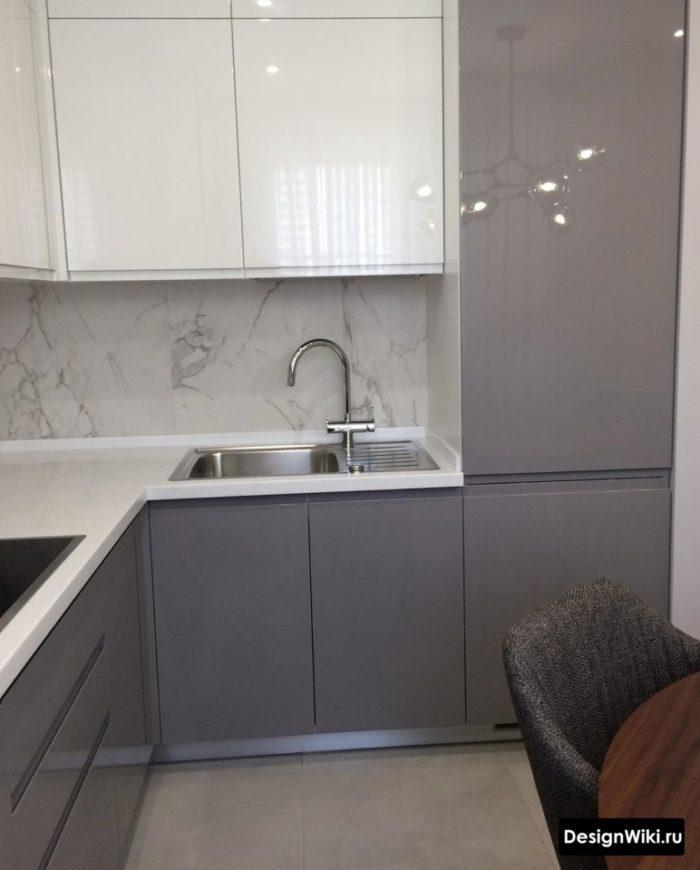 серая угловая кухня со встроенным холодильником