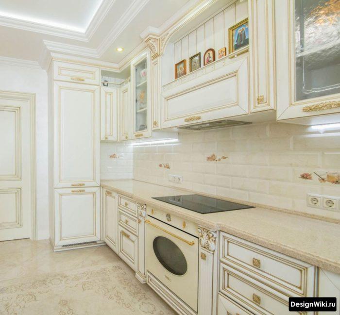 белая с золотом классическая кухня из массива с порталом